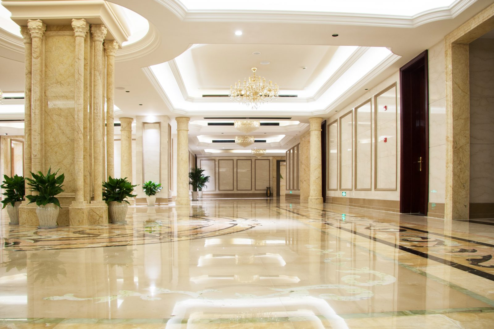 An illuminated hotel lobby with bright lights and marble floors.